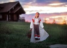 Beautiful girl with a basket of Rowan berries in her hands on the background of the sunset