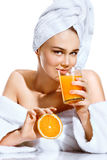 Beautiful girl after bath in white bathrobe and towel on her head. Portrait of smiling girl drinks orange juice and holds orange fruit. Happy and healthy Royalty Free Stock Photography