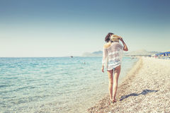 Beautiful girl bathed in sunshine walking on the beach Stock Image