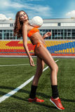 Beautiful girl in a bathing suit on the football field. Royalty Free Stock Images