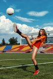 Beautiful girl in bathing suit has foot on the ball. Stock Image