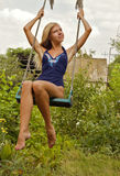 The beautiful girl in a bathing suit on a swing Stock Photo