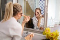 Beautiful girl in bathroom applying makeup royalty free stock photography