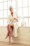 Beautiful girl in bathroom. Beautiful girl in bathrobe is applying body lotion on her legs and smiling while sitting in bathroom Royalty Free Stock Image