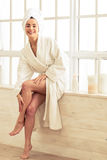 Beautiful girl in bathroom. Beautiful girl in bathrobe is applying body lotion on her legs and smiling while sitting in bathroom Stock Photo