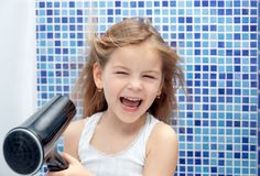 Beautiful girl in the bathroom, blow dry with foams. Little girl. Smiling stock photos