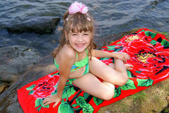 The beautiful girl on a beach. The smiling girl in a green bathing suit sunbathes in the summer on a stone at water Royalty Free Stock Image