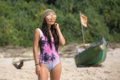Beautiful girl on the beach in bikini. Beautiful girl on the beach on a background of mangroves and a fishing boat Royalty Free Stock Photography