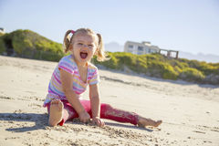 Beautiful girl on a beach on the coast. Playing with the sand Stock Photo