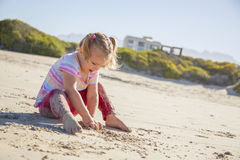 Beautiful girl on a beach on the coast. Playing with the sand Stock Photos