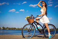 Beautiful girl on the beach with cruiser bicycle. Beautiful young woman on the beach with cruiser bicycle and flowers in basket Stock Images