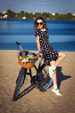 Beautiful girl on the beach with cruiser bicycle. Beautiful young woman on the beach with cruiser bicycle and flowers in basket Stock Photography