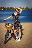 Beautiful girl on the beach with cruiser bicycle. Beautiful young woman on the beach with cruiser bicycle and flowers in basket Royalty Free Stock Image