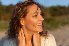 Beautiful girl on a beach. Beautiful curly girl is smiling. Outdoor shoot Royalty Free Stock Photo