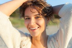 Beautiful girl on a beach. Beautiful curly girl is smiling. Outdoor shoot Royalty Free Stock Image