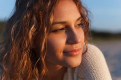 Beautiful girl on a beach. Beautiful curly girl is smiling. Outdoor shoot, sunset Stock Photo