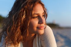Beautiful girl on a beach. Beautiful curly girl is smiling. Outdoor shoot, sunset Royalty Free Stock Image