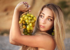 The beautiful girl on beach with grapes. Beautiful woman with grapes on a beach Stock Photo