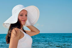 Beautiful girl on the beach in the hat Royalty Free Stock Image