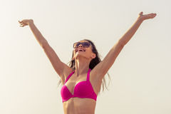 Beautiful girl on the beach. Beautiful girl in pink swimsuit and sun glasses is keeping hands up, looking at the sun and smiling, sky in the background Stock Image