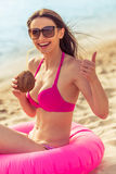 Beautiful girl on the beach. Beautiful girl in pink swimsuit and sun glasses is showing Ok sign, drinking coconut milk, looking at camera and smiling while Stock Image