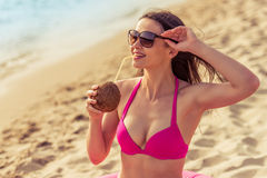 Beautiful girl on the beach. Portrait of beautiful girl in pink swimsuit and sun glasses drinking coconut milk, looking away and smiling while sitting on the Stock Image