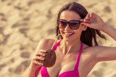 Beautiful girl on the beach. Portrait of beautiful girl in pink swimsuit and sun glasses drinking coconut milk, looking at camera and smiling while sitting on Stock Photos