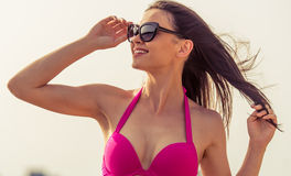 Beautiful girl on the beach. Portrait of beautiful girl in pink swimsuit and sun glasses looking away, enjoying the sun and smiling, sky in the background Royalty Free Stock Photos