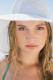 Beautiful girl on the beach smiling in white straw hat and bikini Royalty Free Stock Images