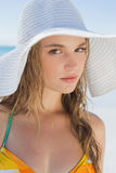 Beautiful girl on the beach smiling in white straw hat and bikini Royalty Free Stock Photos
