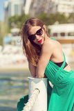 Beautiful girl at the beach. Beautiful girl standing on a pier. Retro look image Royalty Free Stock Photos