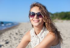 Beautiful girl on a beach. Beautiful girl in sunglasses on a beach. Outdoor shoot Stock Photography