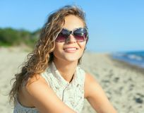 Beautiful girl on a beach. Beautiful girl in sunglasses on a beach. Outdoor shoot Stock Image