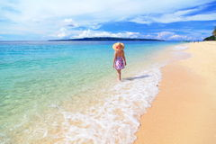 Beautiful girl at the beach with sunny sky, cloud Stock Image