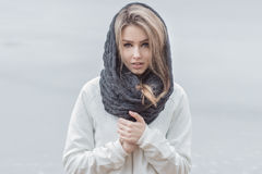Beautiful girl with beautiful lips in a white jacket with a warm scarf on the head in cold weather Royalty Free Stock Images
