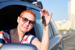 The beautiful girl became the happy owner of the new car. Holds keys in his hands smiling to squinting from the sun. / royalty free stock photo