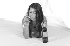 Beautiful girl in bed with a bottle of wine Royalty Free Stock Photography