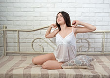 Beautiful girl on the bed stretches sweet and gaily Royalty Free Stock Photo