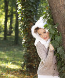 Beautiful girl behind a tree in forest Royalty Free Stock Images