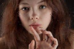 Beautiful girl behind wet window closeup. On dark   background Stock Image