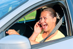 Beautiful girl behind the wheel with phone laughing Stock Photos