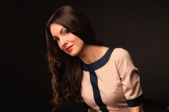Beautiful girl in a beige dress on a dark background Royalty Free Stock Photos