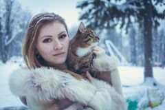 Beautiful girl in a beige short coat with flowing hair holding a cat royalty free stock photo