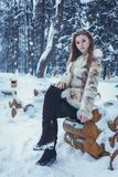 Beautiful girl in a beige short coat with flowing hair is sitting on a wooden frame stock photos
