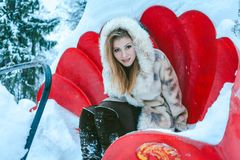 Girl in a beige short coat and hood sits on the red carousel royalty free stock photos