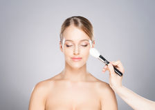 Beautiful girl is being applied with cosmetics Royalty Free Stock Image