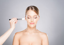 Beautiful girl is being applied with cosmetics Stock Photo