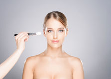 Beautiful girl is being applied with cosmetics Royalty Free Stock Photography