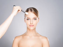 Beautiful girl is being applied with cosmetics Royalty Free Stock Photos