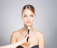 Beautiful girl is being applied with cosmetics Stock Images